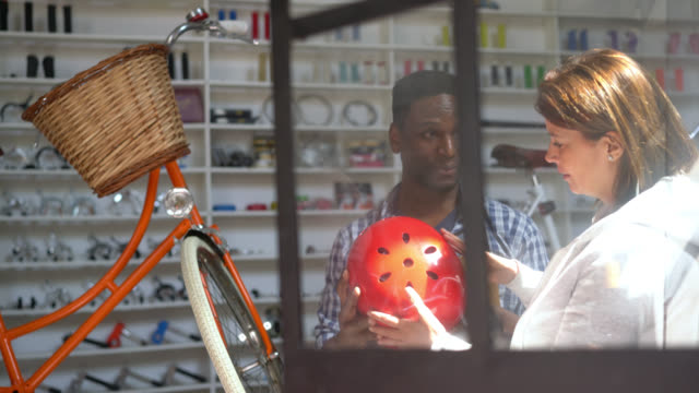 Female customer looking at a helmet at a bicycle store and friendly salesman suggesting her to try it on