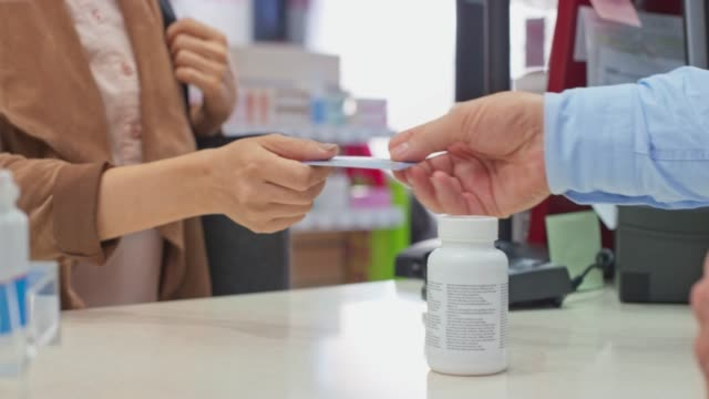 ld female customer paying with a contactless card at the drugstore - pharmacy stock videos & royalty-free footage