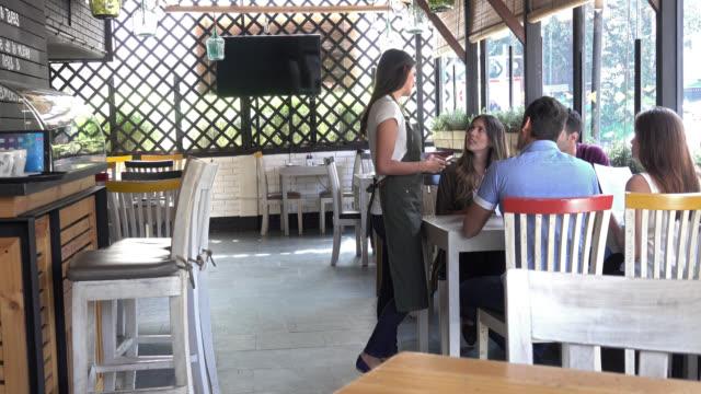 female customer raising hand so her group can order dinner - ordine video stock e b–roll