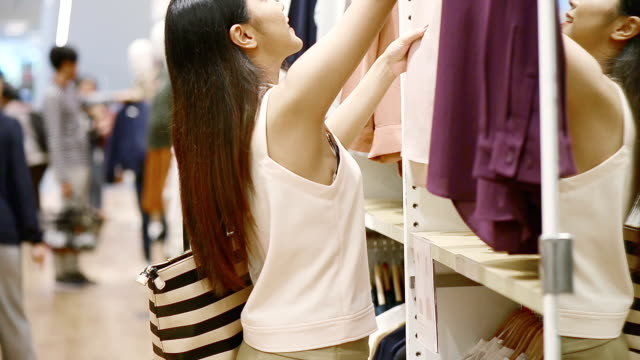 female customer shopping in clothing store - clothing stock videos and b-roll footage
