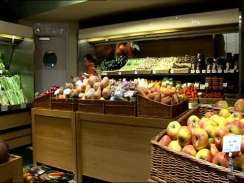 female customer shopping in fruit and vegetable section of organic supermarket / london united kingdom - アナモルフィック点の映像素材/bロール