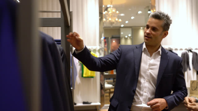 vídeos de stock, filmes e b-roll de cliente feminino falando ao vendedor um terno para seu companheiro e vendedor a ajudá-la - shopping center