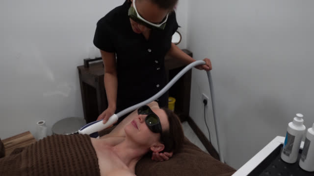 female customer undergoing a laser treatment to remove hairs from armpit at the spa - armpit stock videos and b-roll footage
