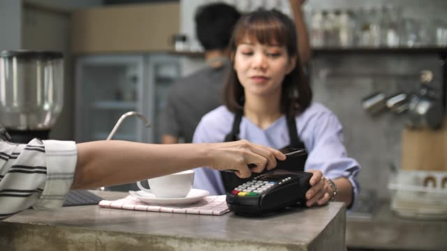 female customer's hand try to pay by smartphone on credit card reader, contactless payment - paying phone stock videos & royalty-free footage