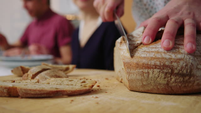 female cutting bread slices for serving to friends at dinner - social gathering stock videos & royalty-free footage