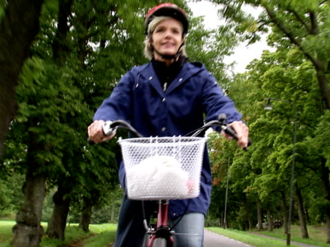 female cyclist in a park stockholm sweden. - cycling helmet stock videos & royalty-free footage