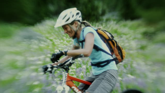 MS SELECTIVE FOCUS Female cyclist resting on flowering meadow, Coast Mountains, Squamish, British Columbia, Canada