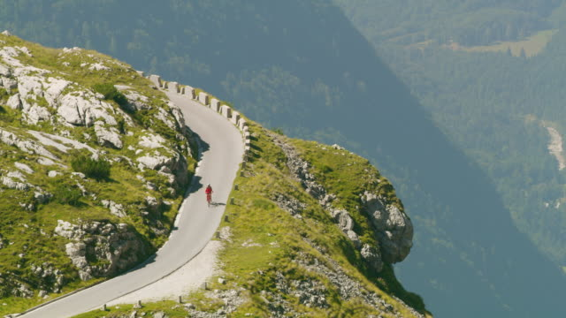 ls female cyclist riding down the mountain road - european alps stock videos & royalty-free footage