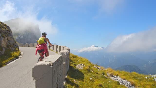 stockvideo's en b-roll-footage met ws vrouwelijke fietser rijden op de bergweg - julian alps