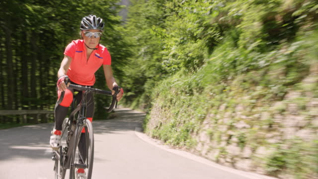 female cyclist speeding down a mountain road in sunshine - bicycle trail outdoor sports stock videos & royalty-free footage