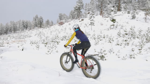 pan ws female cyclists riding fat tire bikes on snow covered trail on winter afternoon - mountain biking stock videos & royalty-free footage
