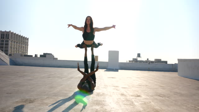 ms female dancer balancing on partners feet while performing on rooftop - tights stock videos & royalty-free footage