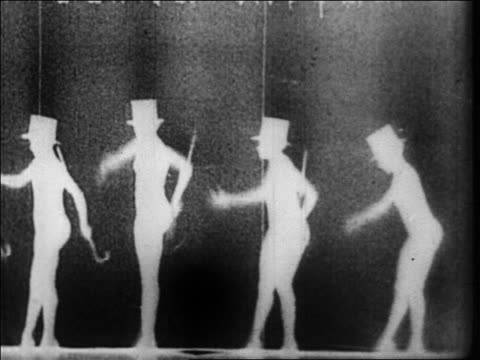 vídeos de stock, filmes e b-roll de b/w 1928 silhouette female dancers with top hats + canes dancing behind screen in nightclub / newsreel - 1920