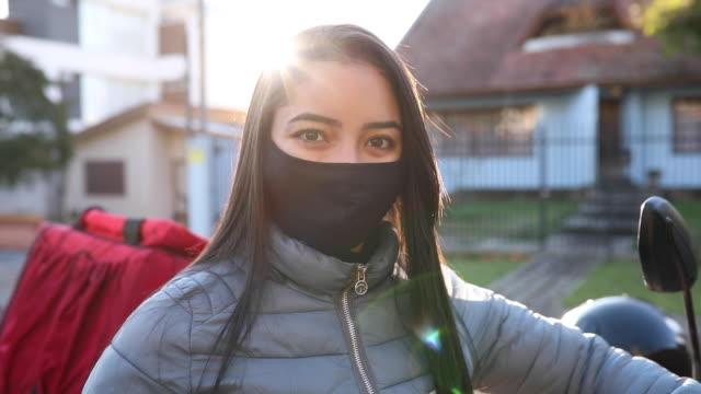 weibliche lieferperson lächelnd hinter maske porträt - motoboy, motogirl - gewerkschaft stock-videos und b-roll-filmmaterial
