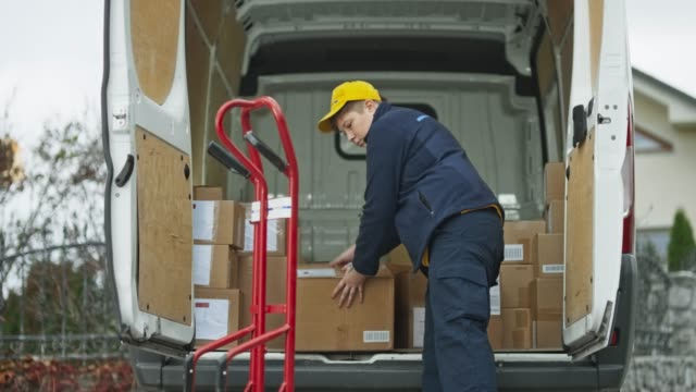 female delivery service driver placing packages onto the cart - commercial land vehicle stock videos & royalty-free footage