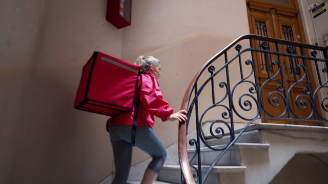 vídeos de stock e filmes b-roll de female delivery worker on steps in residential building searching for customer's apartment - mochila saco
