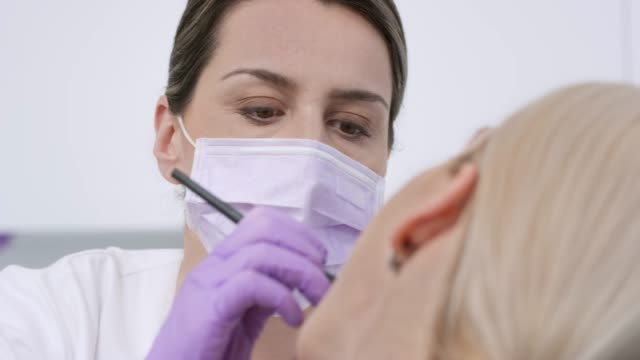 female dentist doing a checkup on the patient's teeth - surgical mask stock videos & royalty-free footage