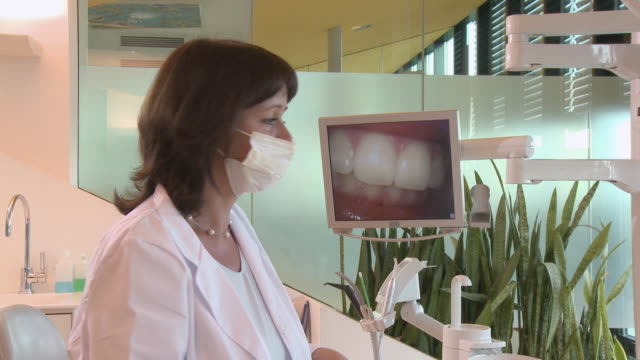 ms female dentist looking at image of teeth on monitor/ dentist turning, removing mask, and smiling at camera/ berlin, germany - dentist stock videos & royalty-free footage