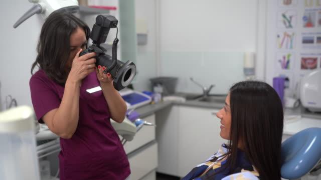 vídeos de stock, filmes e b-roll de dentista feminina tirando foto dos dentes da paciente no consultório do dentista - temas fotográficos
