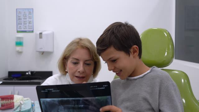 vídeos de stock, filmes e b-roll de dentista fêmea que fala com o paciente novo que explica algo ao ambos olhar um raio x muito alegre - dentista