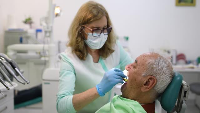 female dentist trying false jaw sample to senior man - human teeth stock videos & royalty-free footage