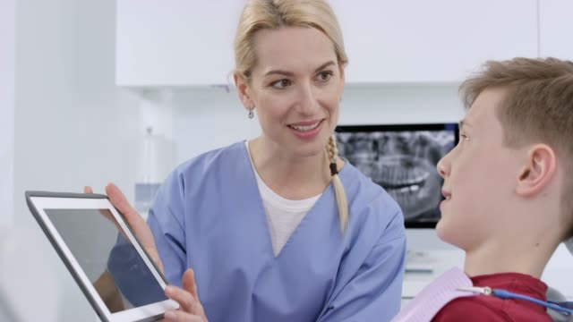 female dentist using the x-ray photos on the digital tablet to show her young male patient the health of his teeth - dental equipment stock videos and b-roll footage