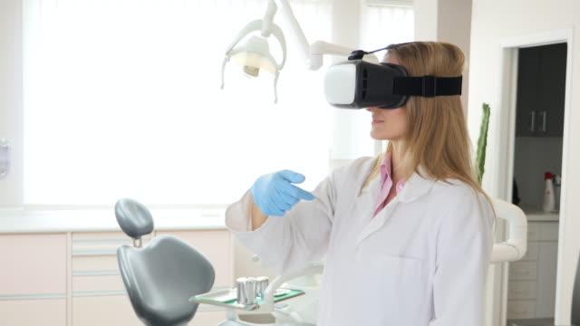 vídeos y material grabado en eventos de stock de dentista mujer con casco de realidad virtual - técnico en urgencias médicas