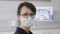 Female dentist wearing surgical mask and loupes