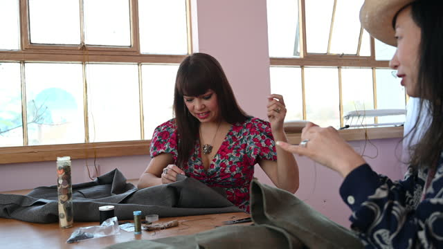 female design professionals hand-sewing together in atelier - workbench stock videos & royalty-free footage
