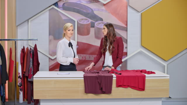 ld female designer and female tv show host presenting the dress designs - pantaloni video stock e b–roll
