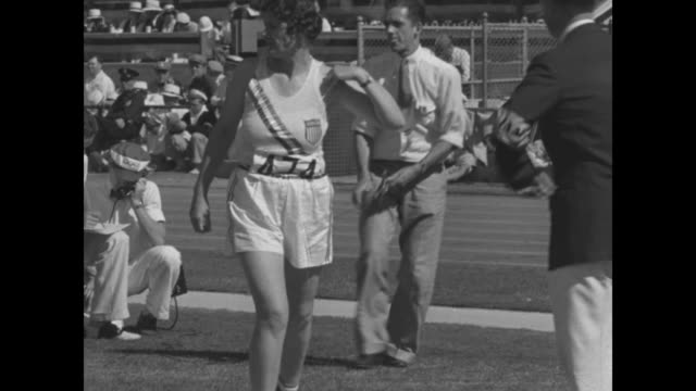 VS female discus throwers on field surrounded by officials audience in stands wind up and throw #474 Ruth Osburn USA / #369 Jadwiga WajsMarcinkiewicz...
