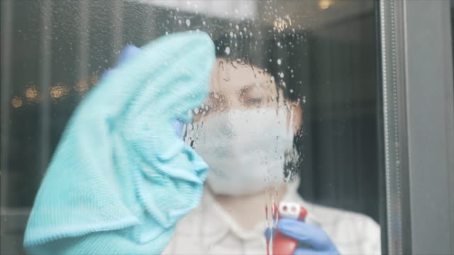 female disinfecting glass door at home. - glove video stock e b–roll