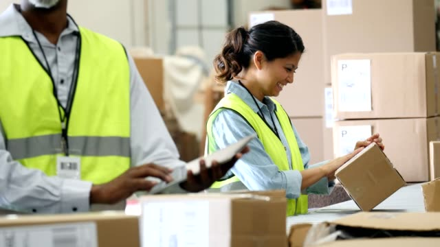 female distribution warehouse employee prepares to send out customer order - labelling stock videos & royalty-free footage