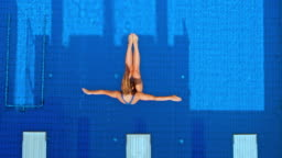 SLO MO CS Female diver diving into the blue pool and rotating in the air