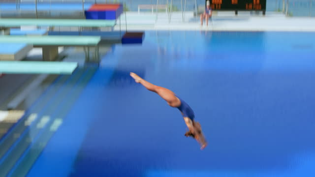 vídeos de stock e filmes b-roll de female diver diving into the pool at a competition on a sunny day - mergulho desporto