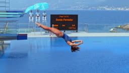 SLO MO Female diver diving into the pool backwards at a competition