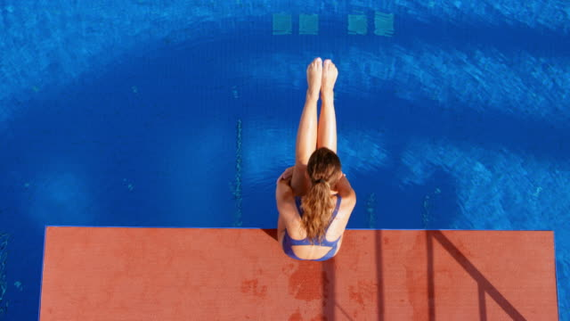 slo mo cs female diver holding her legs up while sitting on the edge of the diving platform and diving into the pool - crane shot stock videos & royalty-free footage