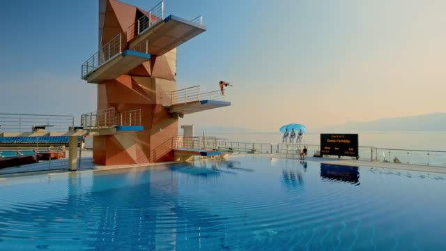 cs female diver jumping from the platform into the tranquil pool at a competition - perfezione video stock e b–roll