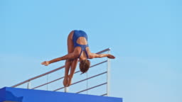 SLO MO Female diver jumping into the pool