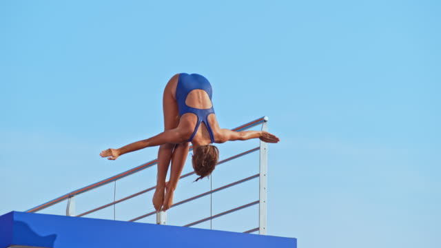 slo mo female diver jumping into the pool - skill stock videos & royalty-free footage