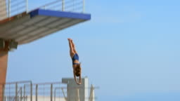SLO MO Female diver jumping off the sunny diving platform
