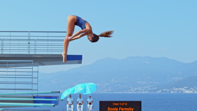 slo mo female diver rotating while diving into the pool at a competition - competizione video stock e b–roll