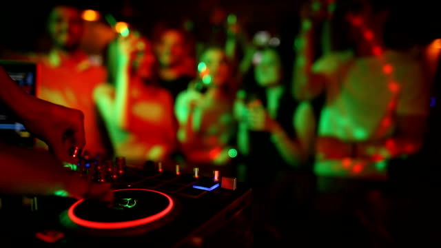 female dj hands mixing on turntable with young people dancing in background. disco club is full when she's breaking the beat - club dj stock videos & royalty-free footage