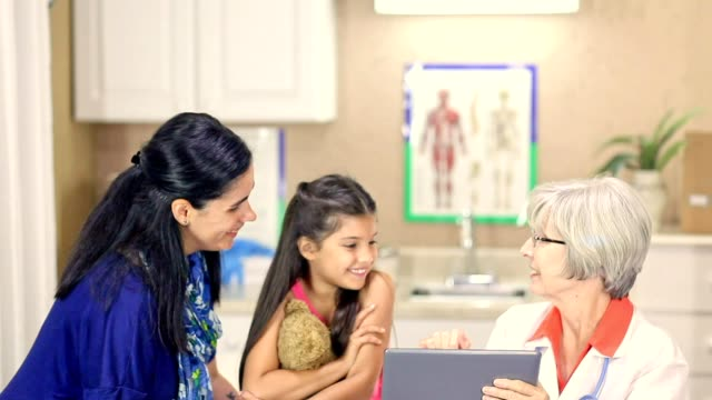 Female doctor and latin descent girl patient in pediatrician's office or clinic.