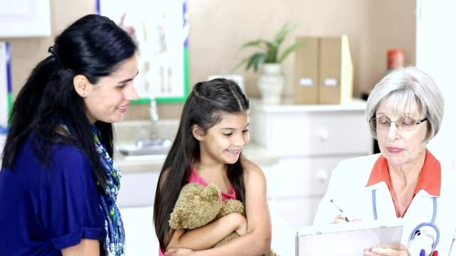 female doctor and latin descent girl patient in pediatrician's office or clinic. - paediatrician stock videos & royalty-free footage