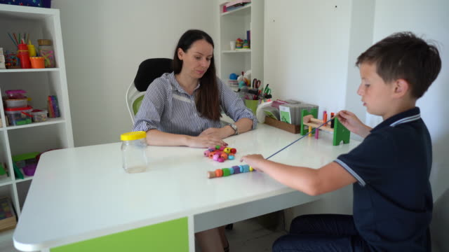 female doctor and little boy on occupational therapy at rehabilitation center - invisible disability stock videos & royalty-free footage