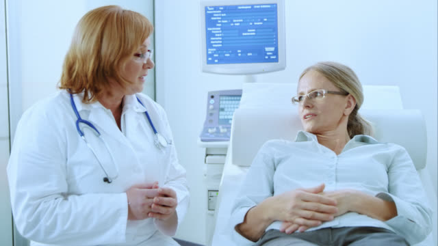 female doctor and patient in examination room having a discussion - 50 59 years stock videos & royalty-free footage