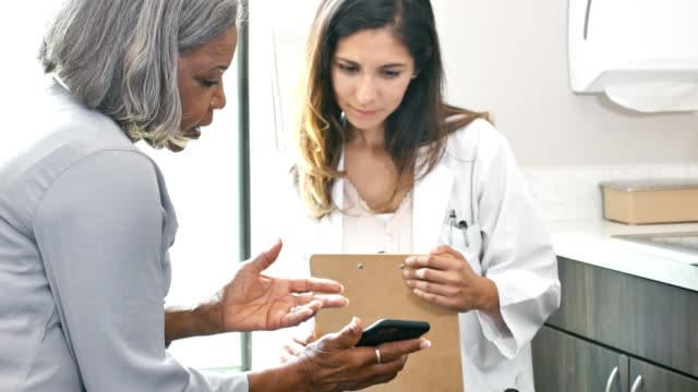 female doctor and patient look at medical data from mobile app - medical record stock videos & royalty-free footage