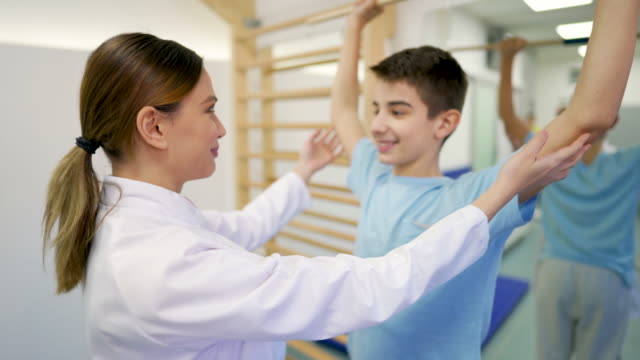 female doctor assists young patient for shoulder exercise - rehabilitation center stock videos & royalty-free footage