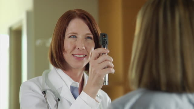 stockvideo's en b-roll-footage met cu female doctor checking eyes of patient and smiling, seattle, washington, usa - oogmeetkunde